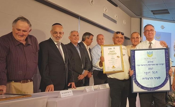 ראש העיר משה פדלון עם דגל היופי. צילום: עיריית הרצליה