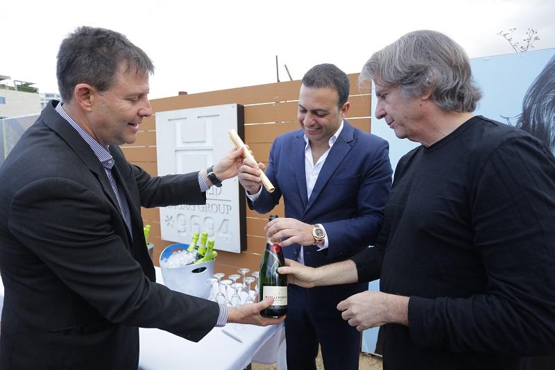 כתב האמנה מוכנס לבקבוק השמפנייה. מימין: דיוויד רוקוול, נציג הבעלים צחי חג'ג' ויגאל צמח. צילום: שי שבירו