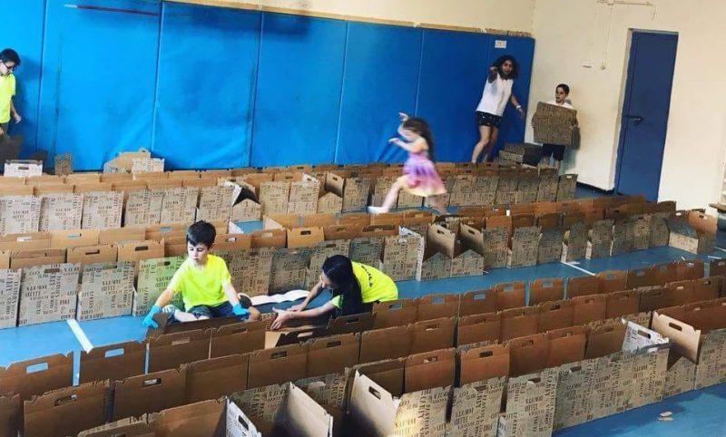 מתנדבי דינל'ה מכינים את החבילות בשבועות