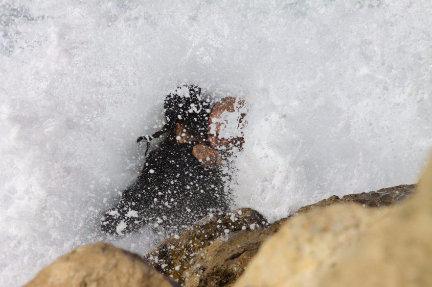 אבן חן אברהם אשאול אוחז בגולש הפצוע ומשאיר אותו מעל המים. צילום ניסים אטון