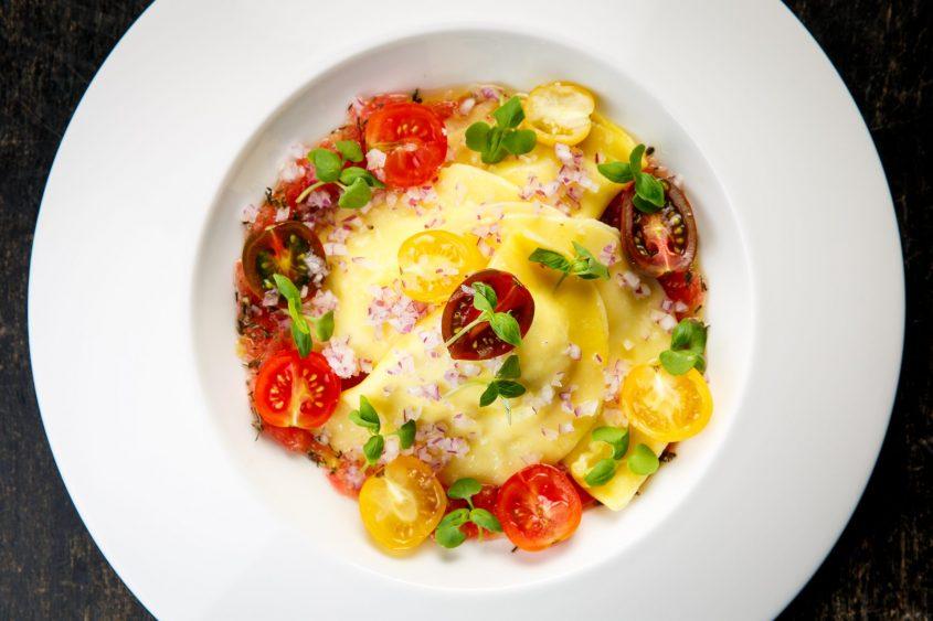 רביולי גבינות משולב רסק עגבניות טריות, בצל סגול, שרי צבעוני, מיקרו בזיליקום ושמן זית. צילום: מתן כץ